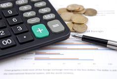 Graphiques, pièces de monnaie avec le stylo et calculatrice Photos stock