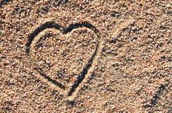 Graphisme de coeur d'amour dans le sable Photo stock