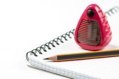 Graphit-hölzerner Bleistift und Bleistiftspitzer auf dem Schule-notebo Stockfoto