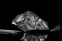 Graphit rough mineral stone, pencil leads and pencil, black back. Ground, reflections Royalty Free Stock Photos