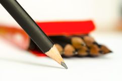 Graphite pencil. On a white sheet on a background of the box with pencils, macro Royalty Free Stock Image