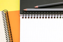 Graphite pencils, open multicolor notebooks on yellow surface ba Stock Photography