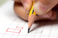 Graphomotor skills. Education concept. The hand writes rectangle. Close up. Royalty Free Stock Photos
