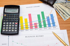 Graphs, charts, business table with money, calculator and pen. On table Royalty Free Stock Images