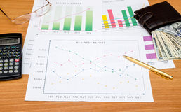 Graphs, charts, business table with money, calculator. And pen on table Royalty Free Stock Photo