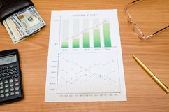 Graphs, charts, business table with money, calculator and pen. On table Stock Photo