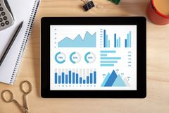 Graphs and charts elements on tablet screen with office objects. On wooden desk. All screen content is designed by me. Top view Royalty Free Stock Images
