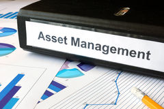 Graphs and file folder with label Asset Management. Business concept Stock Photos