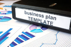 Graphs and file folder with label Business plan template. Stock Photo