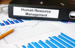 Graphs and file folder with label Human Resource Management. Business concept Royalty Free Stock Image