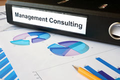Graphs and file folder with label Management Consulting. Stock Photography