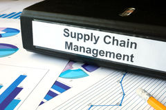 Graphs and file folder with label supply chain managment. Stock Photos