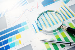 Graphs, magnifier and pen. Royalty Free Stock Photo
