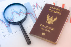 Graphs, magnifier and Thailand passport Stock Image