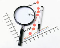 Graphs and Magnifying glass Stock Images