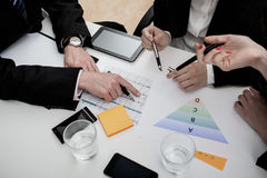 Graphs and notes. Business people analysing graphs and making notes Stock Photography
