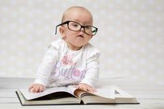 Grappig babymeisje die een boek lezen Stock Foto