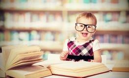 Grappig babymeisje die in glazen boek in bibliotheek lezen