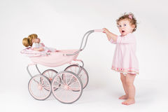 Grappig babymeisje die met een poppenwandelwagen lopen Stock Foto's