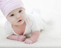 Grappig babymeisje die op wit liggen Royalty-vrije Stock Fotografie