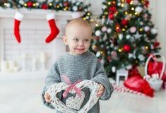 Grappig babymeisje met giftdozen en Kerstboom op achtergrond Stock Afbeeldingen