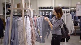Grappig beeld Een meisje in een kledingsopslag kiest een uitrusting De vrouw wordt geschokt door dure prijzen, koestert zij terug stock videobeelden