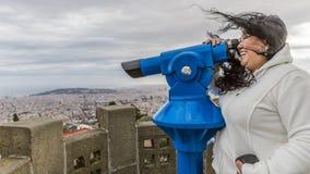 Grappig beeld van een glimlachende vrouw met haar die haar door de wind wordt verfomfaaid die door een telescoop waarnemen royalty-vrije stock fotografie
