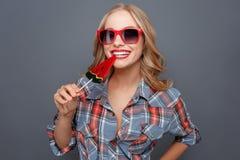 Grappig beeld van meisje die de lolly bijten Zij glimlacht Ook draagt deze dame donkere glazen met rode rand geïsoleerde Royalty-vrije Stock Afbeeldingen