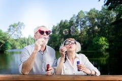 Grappig bejaarde die de rode zonnebril dragen die van de hartvorm zeepbels gebruiken royalty-vrije stock fotografie