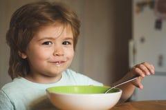 Grappig eet Weinig baby De gelukkige babyjongen eet gezonde voedsellepel zelf Voedsel en Drank voor Kind Het leuke jonge geitje i stock afbeeldingen