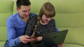 Grappig emotioneel paar om online te winkelen en door krediet plastic kaart te betalen stock video