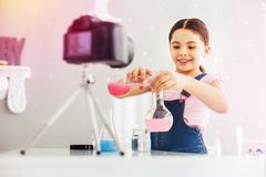 Grappig en slim meisje die jumpsuit gietende roze substanties dragen in reageerbuis stock foto's