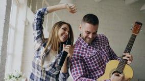 Grappig gelukkig en houdend van paar die en het spelen gitaar dansen De man en de vrouw hebben pret thuis tijdens hun vakantie Stock Foto