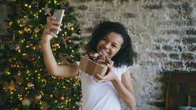 Grappig gemengd rasmeisje die selfie beelden op smartphonecamera thuis nemen dichtbij Kerstboom Royalty-vrije Stock Afbeelding