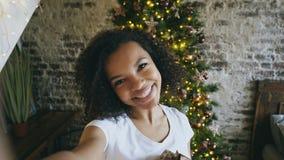 Grappig gemengd rasmeisje die selfie beelden op smartphonecamera thuis nemen dichtbij Kerstboom royalty-vrije stock fotografie