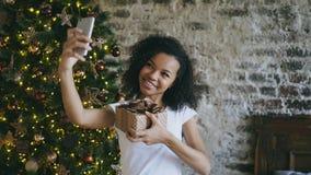 Grappig gemengd rasmeisje die selfie beelden op smartphonecamera thuis nemen dichtbij Kerstboom Royalty-vrije Stock Foto