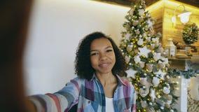 Grappig gemengd rasmeisje die selfie beelden op smartphonecamera thuis nemen dichtbij Kerstboom Stock Foto's
