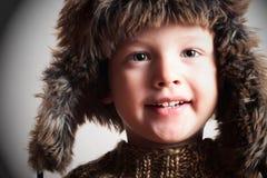 Grappig glimlachend kind in een bonthoed. manierjong geitje. de winterstijl. weinig jongen. kinderen Royalty-vrije Stock Afbeeldingen