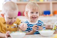Grappig glimlachend weinig jong geitje die in kleuterschool eten royalty-vrije stock fotografie