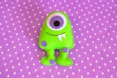 Grappig groen monster dat op het purpere patroon van de stoffenstip wordt gevoeld Het naaien concept Stock Foto
