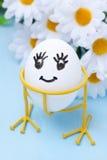 Grappig het glimlachen ei op tribune en bloemen voor Pasen, close-up Royalty-vrije Stock Foto's