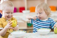 Grappig het glimlachen jong geitje die appel in kleuterschool eten stock afbeeldingen