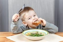 Grappig jong geitje met stuk van brood en plaat van soep Stock Foto's