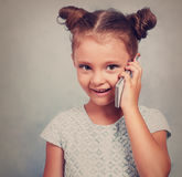 Grappig jong geitjemeisje die op mobiele telefoon met gelukkige glimlach op blauw spreken stock foto's