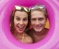 Grappig jong gelukkig strandpaar die in het midden van roze opblaasbare ring glimlachen Stock Afbeeldingen