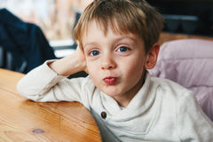 grappig Kaukasisch weinig jongenspeuter die in wit overhemd makend gezichten glimlachen stock foto's