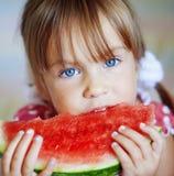 Grappig kind dat watermeloen eet stock foto