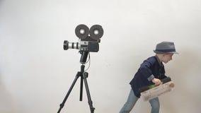 Grappig kind die een dakspaan, weinig directeur houden die pret, oude camera, actie hebben stock videobeelden