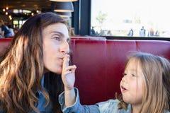 Grappig kind die en een gebraden aardappel eten geven aan haar moederzitting in restaurant royalty-vrije stock fotografie