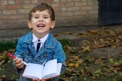 Grappig kind die in notitieboekje schrijven die potlood en het glimlachen gebruiken Twee of drie jaar oud jong geitje die zich op royalty-vrije stock foto's
